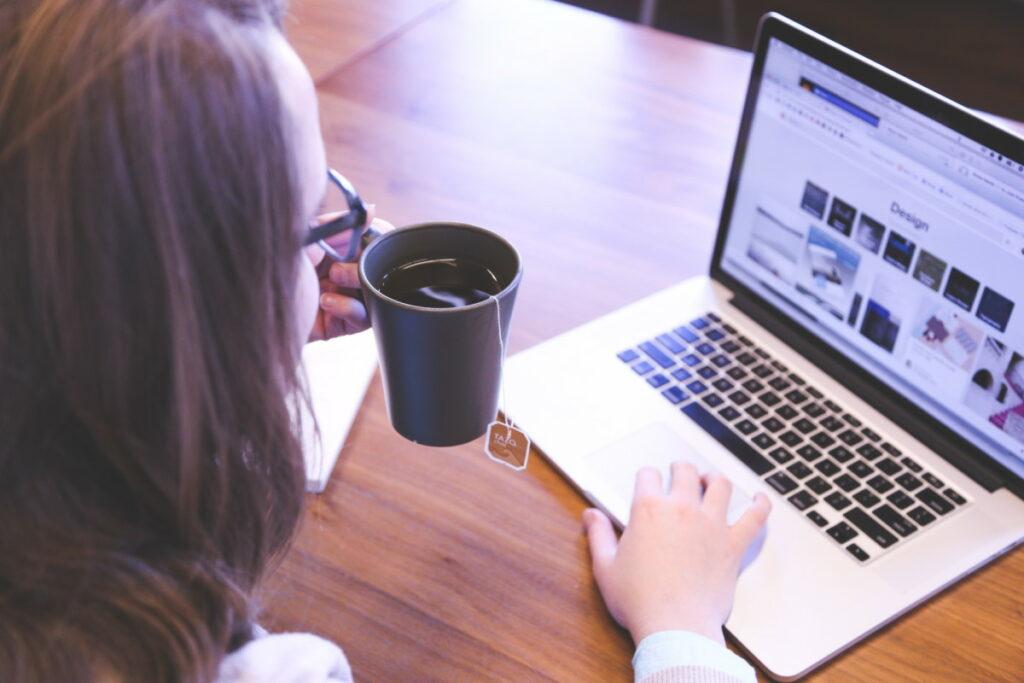 Frau sitzt mit einer Tasse Tee vor einem Laptop
