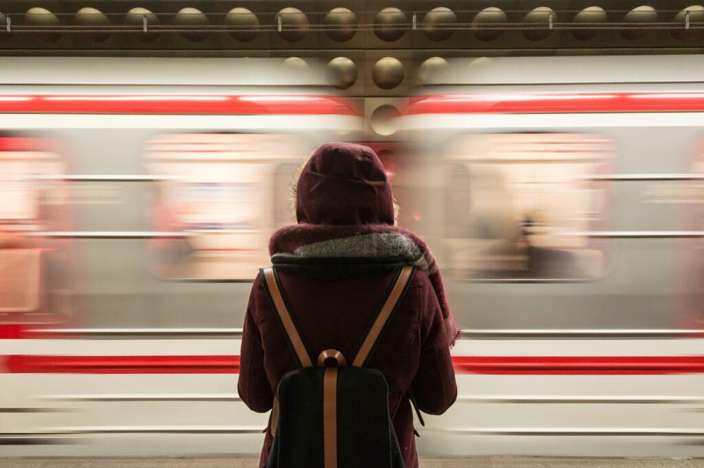 Eine Person steht vor einem durchfahrenden Zug