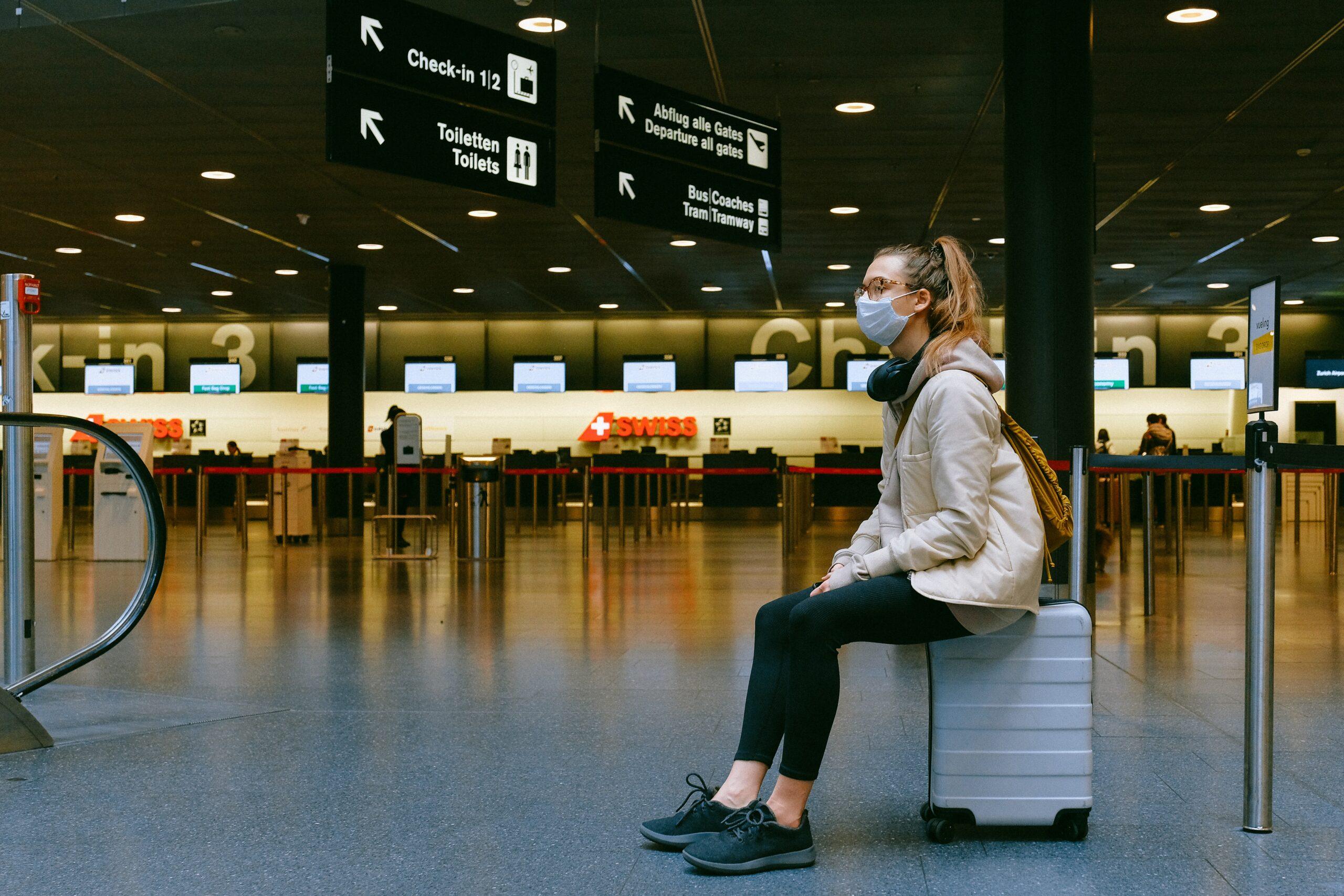 Frau mit Mundschutz sitzt auf ihrem Gepäck
