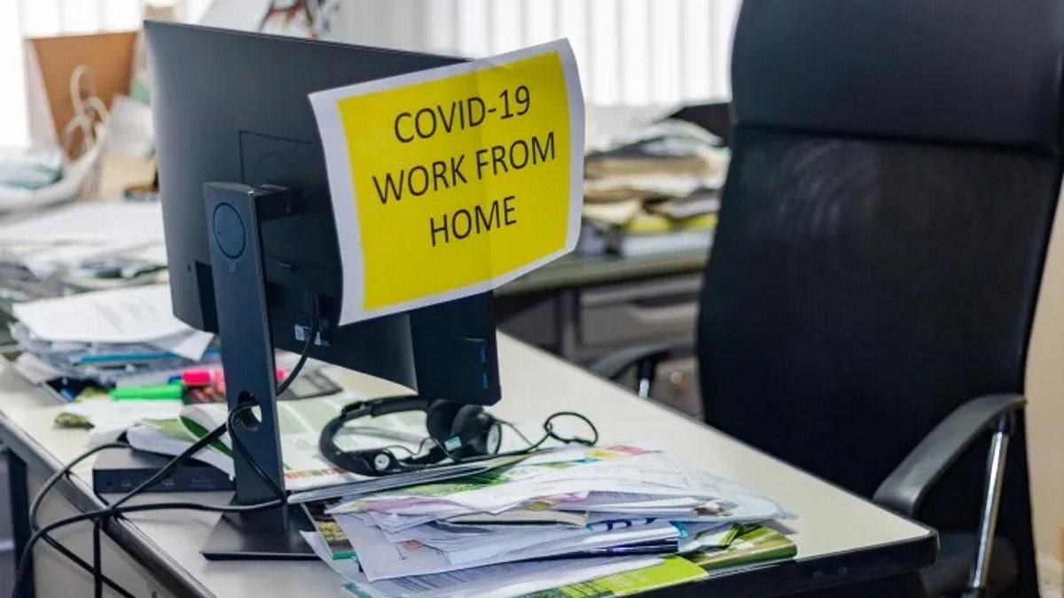 """Zettel mit Aufschrift """"COVID-19 - Work from home"""" hängt an einem Monitor"""